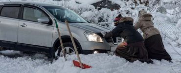 Two women attempt to get a car unstuck from a snowbank