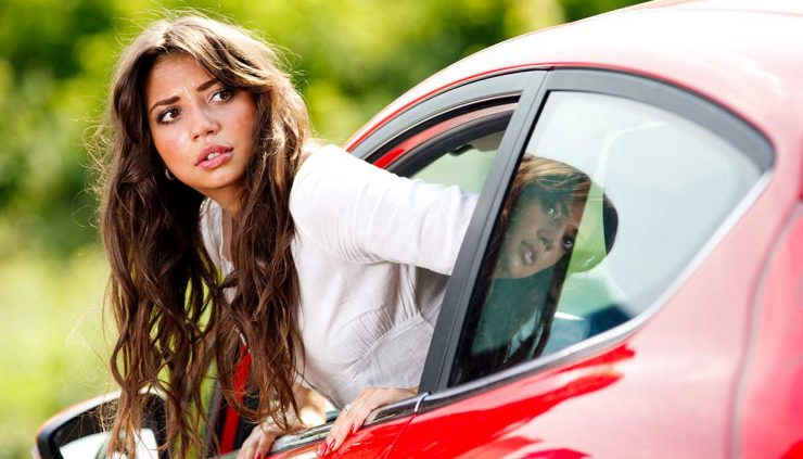 Beautiful young woman looks out the window of her car to see if she hit something