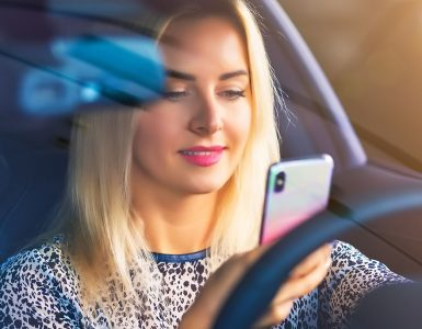 woman looking at cell phone while driving